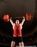 Picture of a weightlifter holding barbells over his head after doing a deadlift or clean and jerk. Orange colored barbell weights and a body builder wearing black shorts and an orange tank top during his weight lifting competition.
